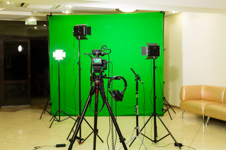 The camera on the tripod, led floodlight, headphones and a directional microphone on a green background. The chroma key. Green screen