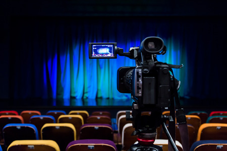 The LCD display on the camcorder. Videography in the theater. Blue-green curtain on the stage. Stock Photo
