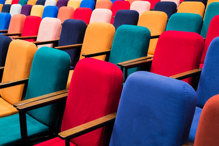 The auditorium in the theater. Multicolored spectator chairs.