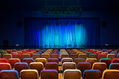 The auditorium in the theater. Blue-green curtain on the stage. Multicolored spectator chairs. Lighting equipment.