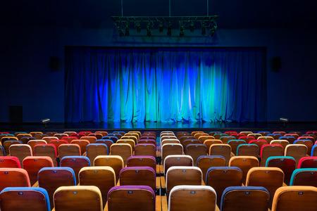 L'auditorium dans le théâtre. Rideau bleu-vert sur la scène. Chaises de spectateurs multicolores. Matériel d'éclairage Banque d'images - 92501177
