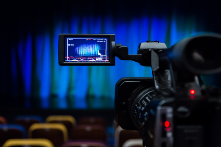 The LCD display on the camcorder. Shooting theatrical performances. The TV camera. Colorful chairs in the auditorium. Stock Photo
