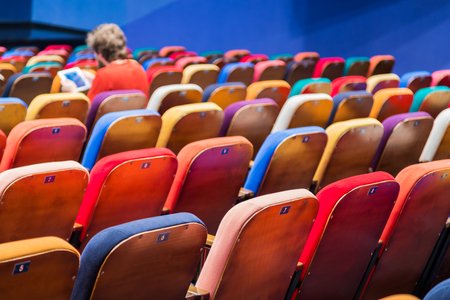 The auditorium in the theater. Multicolored spectator chairs. One person in the audience.