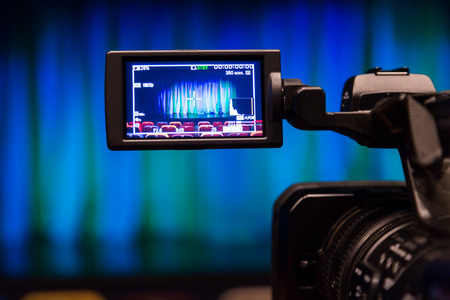 The LCD display on the camcorder. Videography in the theater. Blue-green curtain on the stage. Stock Photo - 92501397