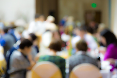 The image is not in focus. The people at the Banquet tables at the event. The food and drinks. New years corporate.