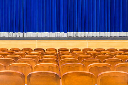 The auditorium in the theater. Blue curtain on the stage. Blue-brown chair. Room without people.