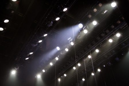 Lighting equipment on the stage of a theater or concert hall. The rays of light from spotlights. Halogen and led light bulbs. Lens lighting