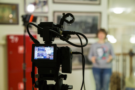 TV shooting at the Museum. LCD monitor on the camcorder. The girl in front of the camera. A record of the interview. Filming equipment and lighting equipment.