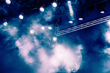 Blue light rays from the spotlight through the smoke at the theater or concert hall. Lighting equipment for a performance or show 스톡 콘텐츠
