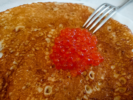 Russian pancakes with red caviar. Delicious food at the carnival. Stock Photo
