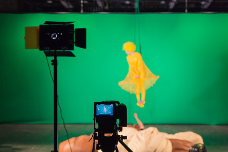 Actress in yellow dress starred in a movie on a green background. Key in the film industry. Chromakey.