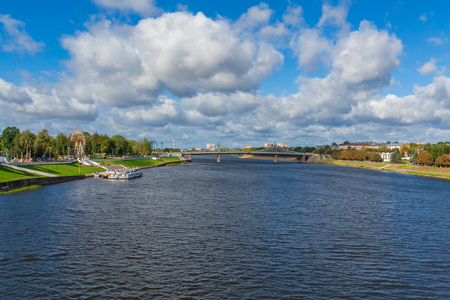 Río Volga cerca de Tver, Rusia. El viejo puente del Volga en el horizonte. Embarcaciones de recreo de pasajeros en el muelle. Pintoresco paisaje fluvial. Día soleado de otoño.