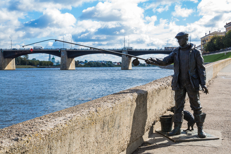 The monument to the fisherman and the cat on the embankment of the river Volga in Tver, Russia. Picturesque clouds in the sky. Road bridge on the horizon. Summer or autumn Sunny day.