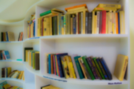 Defocused image, bokeh effect. Books on the shelves in the library.