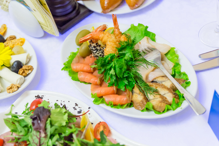 Cold appetizers, seafood and green vegetables at the Banquet table in the restaurant.