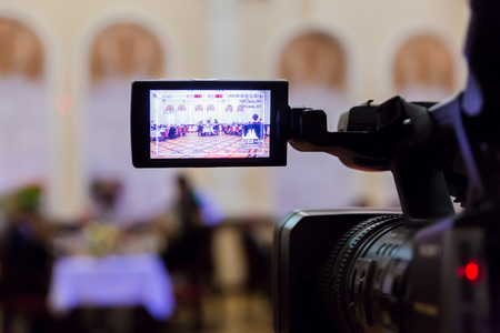 Video shooting at the restaurant. Digital video camera with LCD display. At the background. Defocused background.