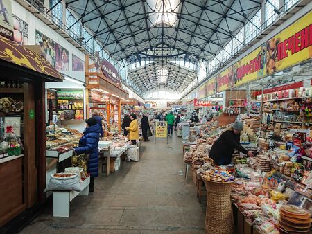 Saratov / Russia - January 26, 2019: Covered market. Ancient building, built in 1916. Sale of various food products. People, buyers and sellers. 新聞圖片