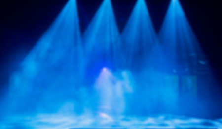Blue rays of light from the spot. Theatrical performance. Defocused abstract image. Texture background.