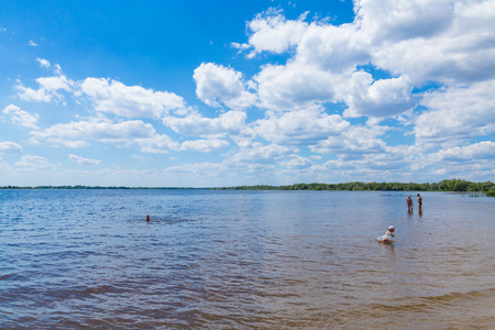 People swim in the river on the beach. Sunny summer day. Picturesque clouds in the sky. River landscape.