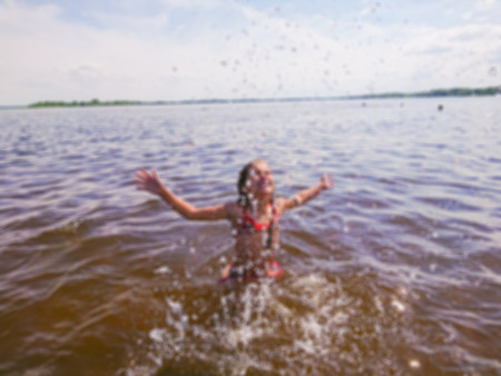Defocused abstract image. Six-eight-year-old girl swimming in the river. Water splashes against the sky. River landscape. Stok Fotoğraf - 120726873