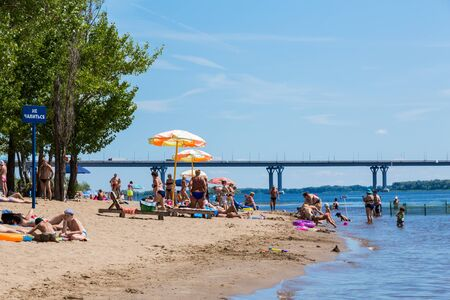 Saratov / Russia - July 6, 2018: People sunbathe and swim in the sandy beach. On a sunny summer day. Road bridge on the horizon. 新聞圖片