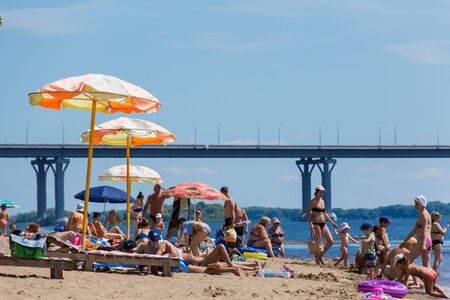 Saratov / Russia - July 6, 2018: People sunbathe and swim in the sandy beach. On a sunny summer day. Road bridge on the horizon. 版權商用圖片 - 137904249