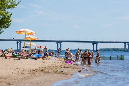 Saratov / Russia - July 6, 2018: People sunbathe and swim in the sandy beach. On a sunny summer day. Road bridge on the horizon. Redactioneel