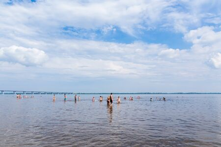Saratov / Russia - July 7, 2018: People sunbathe and swim in the sandy beach. On a sunny summer day. Road bridge on the horizon. Archivio Fotografico - 137904253