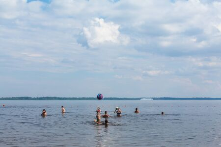 Saratov / Russia - July 7, 2018: Sandy river beach. On a sunny summer day. Children and adults play ball in the water.
