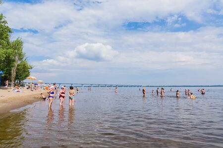 Saratov / Russia - July 7, 2018: People sunbathe and swim in the sandy beach. On a sunny summer day. Road bridge on the horizon.