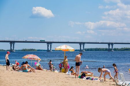 Saratov / Russia - July 5, 2018: People sunbathe and swim in the sandy beach. On a sunny summer day. Road bridge on the horizon. 新聞圖片