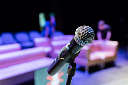 Wireless microphone on the stand. Blurred background. People in the audience. Show on stage in the theater or concert hall. Stok Fotoğraf
