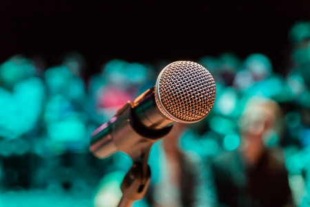 Wireless microphone on the stand. Blurred background. People in the audience. Show on stage in the theater or concert hall. Stock Photo