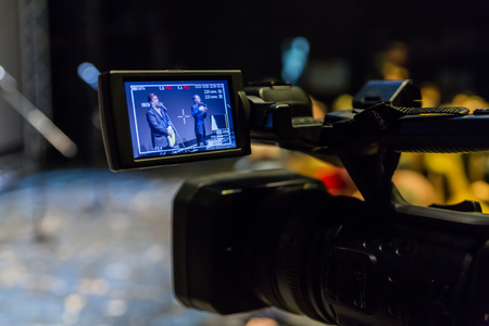 Video shooting of the event. Camcorder with LCD display. Microphones on a gray screen background.