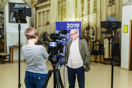 Saratov / Russia - February 20, 2019: The girl interviews the man. Video shooting in the interior. LCD display on the camcorder. 新聞圖片