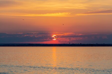 Sunset on the Volga river in Russia in July. Orange sun in the sky. Picturesque nature. Summer evening. River cruise. Stok Fotoğraf