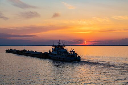 A tug on the river pushes a barge with sand or gravel. Sunset on the Volga river in Russia in July. Orange sun in the sky. Picturesque nature. Summer evening. River cruise. Stok Fotoğraf - 131890564