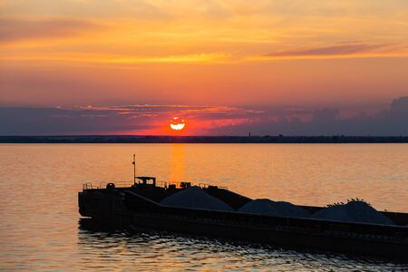 A tug on the river pushes a barge with sand or gravel. Sunset on the Volga river in Russia in July. Orange sun in the sky. Picturesque nature. Summer evening. River cruise.