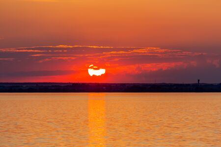 Sunset on the Volga river in Russia in July. Orange sun in the sky. Picturesque nature. Summer evening. River cruise. Stok Fotoğraf - 131891287