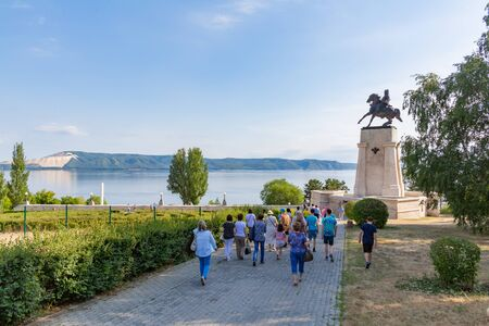 Togliatti, Samara region / Russia - July 2, 2019: Tourists on the background of the monument to the founder of the city Vasily Nikitich Tatishchev. Volga river and Zhiguli mountains on the horizon 新聞圖片