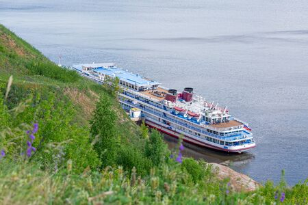 Picturesque river landscape. Four-deck cruise ship at the pier. The view from the top. Volga River, Russia, Tatarstan.
