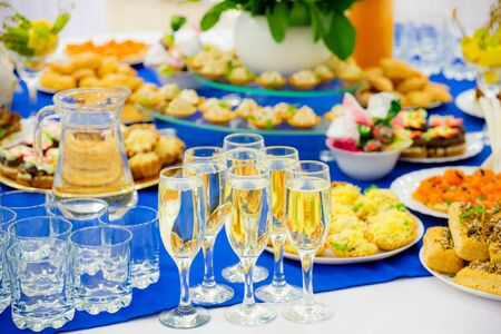 White sparkling wine in glasses. Festively laid tables at the Banquet. Various delicacies, snacks and drinks. Catering.
