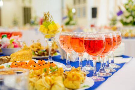 Vino rosato in bicchieri. Tavole apparecchiate a festa al banchetto. Varie prelibatezze, snack e bevande. Ristorazione.