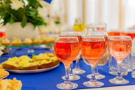 Festively laid tables at the Banquet. Various delicacies, snacks and drinks. Catering. Pink wine in glasses.