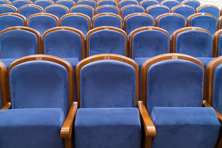 Blue plush chairs in the auditorium of the theater. The interiors of the concert hall.