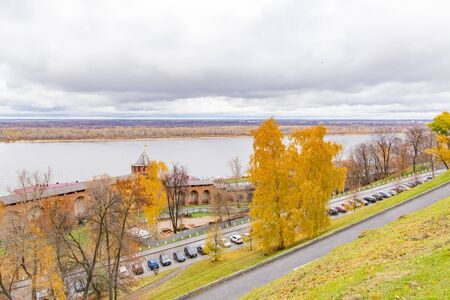 Embankment of the Volga river in Nizhny Novgorod. The Kremlin walls are made of red stone. Car parking. Autumn cloudy day. Yellow trees. Stok Fotoğraf - 132488550