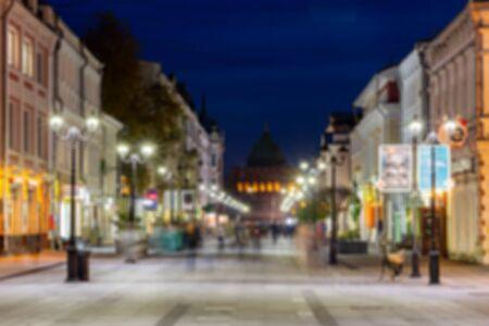 Defocused image, bokeh effect. Evening or night cityscape. Long exposure. People walk on a pedestrian street. Nizhny Novgorod, Russia. 版權商用圖片