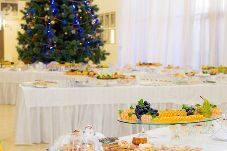 Various fruits, desserts, pastries on the holiday table. New year or Christmas. Decorated Christmas tree.