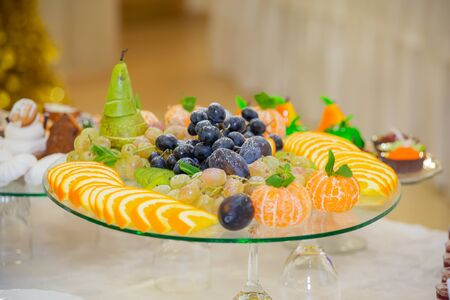 Various fruits, desserts, pastries on the holiday table. New year or Christmas.
