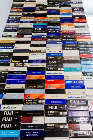 Saratov / Russia - February 15, 2020: A stack of videotapes in VHS format. Colorful boxes of cassettes. 新聞圖片